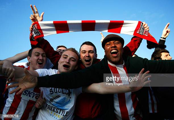 Brentford fans celebrate after their team scored in the last minute to draw the match during the npower League One Play Off Semi Final match between...