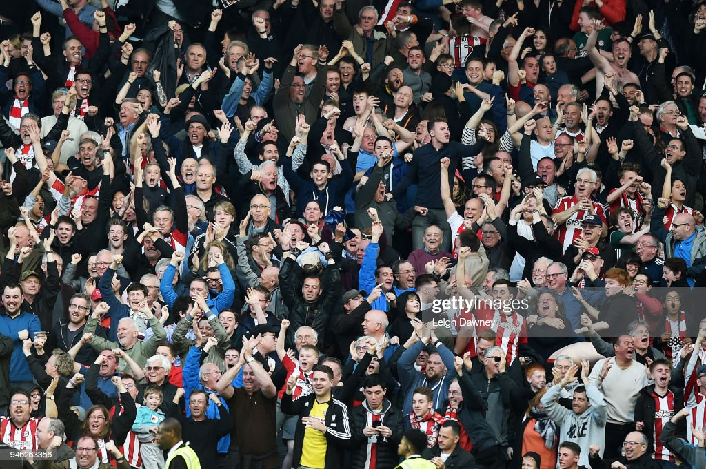 Brentford fans celebrate after their team scored the equalising goal during the Sky Bet Championship match between Fulham and Brentford at Craven Cottage on April 14, 2018 in London, England.