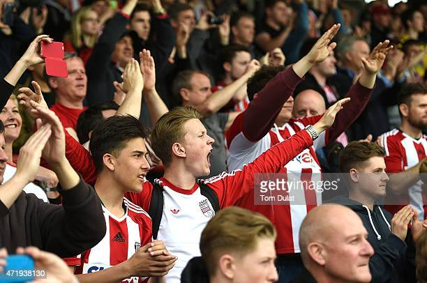 Brentford fans celebrate during the Sky Bet Championship match between Brentford and Wigan Athletic at Griffin Park on May 2 2015 in Brentford England