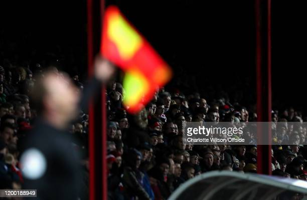 Brentford fans in eerie light at Griffin Park as the linesman calls a throwin during the Sky Bet Championship match between Brentford and Leeds...