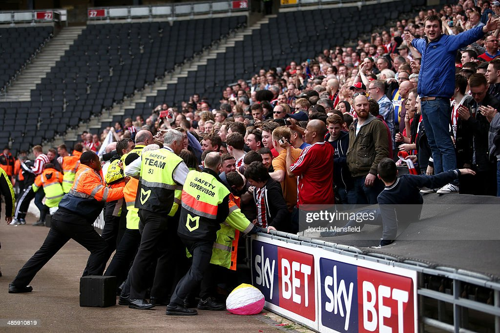 Brentford FC fans push their way past crowd-control to invade the pitch at the final whistle during the Sky Bet League One match between MK Dons and Brentford at Stadium mk on April 21, 2014 in Milton Keynes, England.