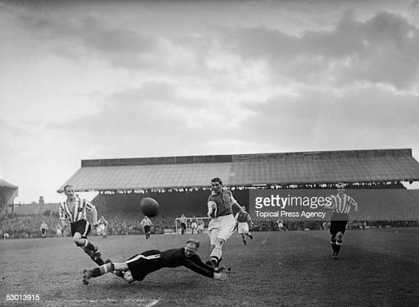 Brentford goalkeeper Crozier dives to the feet of Arsenal's Ted Drake in an attempt to save the shot during a match at Brentford, 8th September 1938.