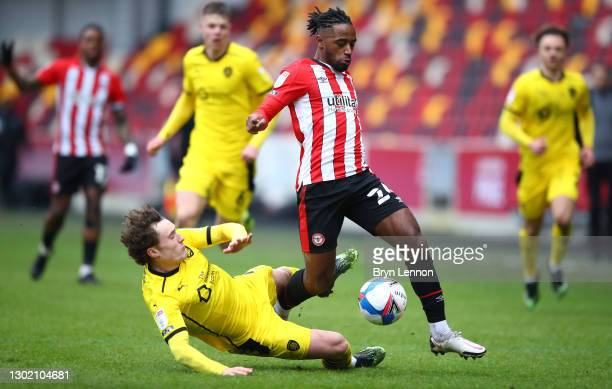 Brentford player Tariqe Fosu skips the challenge of Barnsley player Callum Styles during the Sky Bet Championship match between Brentford and...