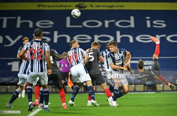 Brentford's Danish midfielder Emiliano Marcondes goes airborne to kick the ball to score the equalising goal during the English League Cup third...