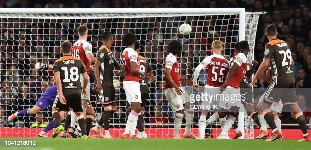 Brentford's Irish midfielder Alan Judge scores his team's first goal from a freekick during the English League Cup third round football match between...