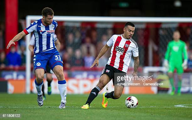 Brentford's Nico Yennaris holds off the challenge from Wigan Athletic's Yanic Wildschut during the Sky Bet Championship match between Brentford and...