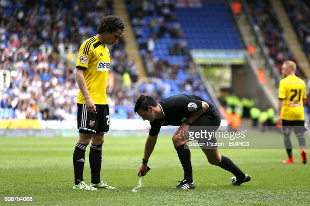 Brentford's Ramallo Jota watches as referee Andy Madley lays down the vanishing spray