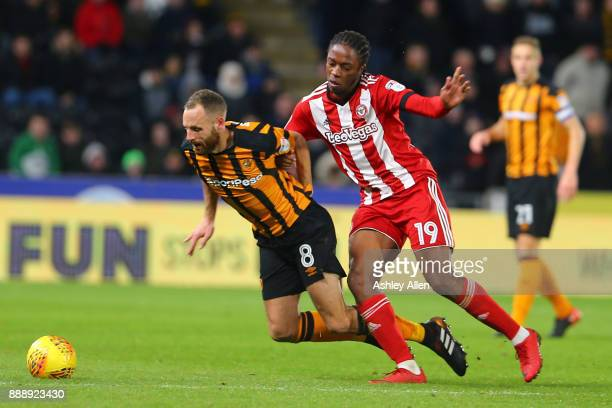 Brentford's Romaine Sawyers tackles Hull City's David Meyler during the Sky Bet Championship match between Hull City and Brentford at KCOM Stadium on...