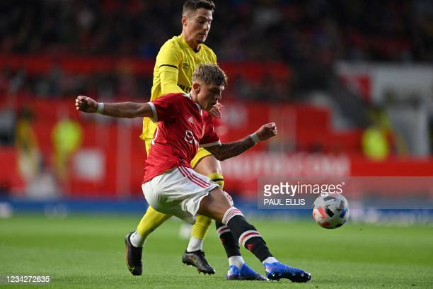 Brentford's Spanish striker Sergi Canos vies with Manchester United's English defender Brandon Williams during the English Premier League friendly...