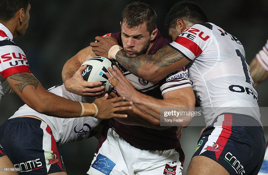Brenton Lawrence of the Sea Eagles is tackled by the Roosters defence during the NRL trial match between the Manly Sea Eagles and the Sydney Roosters at Bluetongue Stadium on February 16, 2013 in Gosford, Australia.