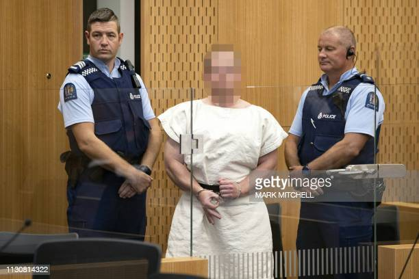 TOPSHOT Brenton Tarrant the man charged in relation to the Christchurch massacre makes a sign to the camera during his appearance in the Christchurch...