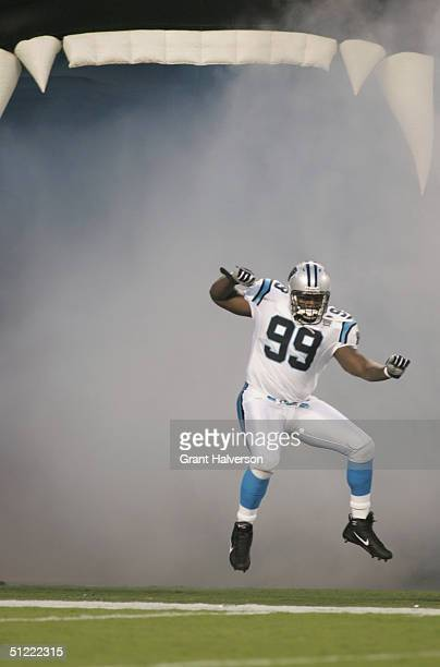 Brentson Buckner of the Carolina Panthers jumps out from the fog pouring out of the mouth of an inflated panther as he is introduced before the game...