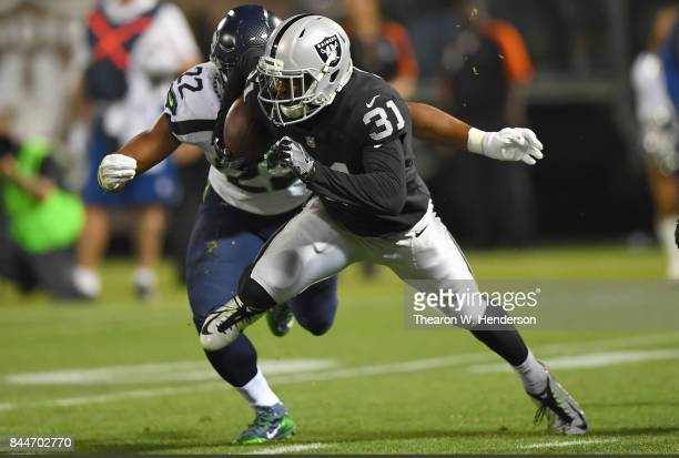 Breon Borders of the Oakland Raiders runs with the ball while pursued by CJ Prosise of the Seattle Seahawks during the second quarter at...