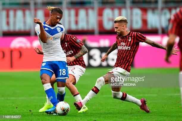 Brescia's French forward Florian Aye vies with AC Milan's Spanish forward Samu Castillejo during the Italian Serie A football match AC Milan vs...