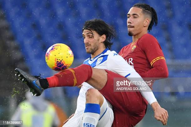 Brescia's Italian forward Ernesto Torregrossa and Roma's English defender Chris Smalling go for the ball during the Italian Serie A football match...