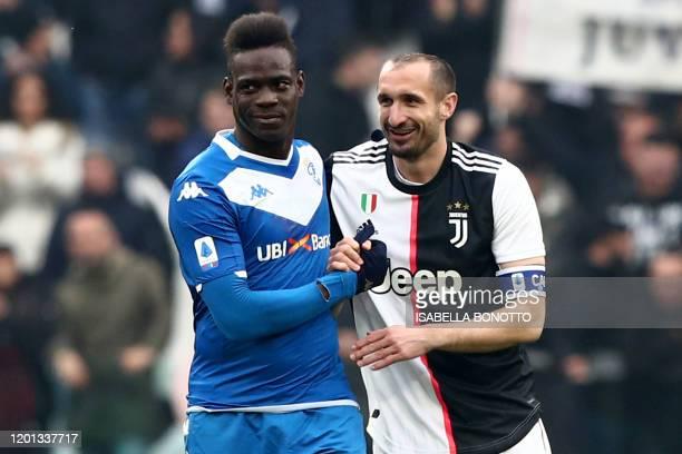 Brescia's Italian forward Mario Balotelli greets Juventus' Italian defender Giorgio Chiellini after he entered the pitch during the Italian Serie A...