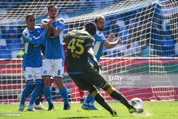 Brescia's Italian forward Mario Balotelli shoots a free kick as Napoli's Spanish forward Jose Callejon Napoli's Spanish defender Fabian Ruiz and...