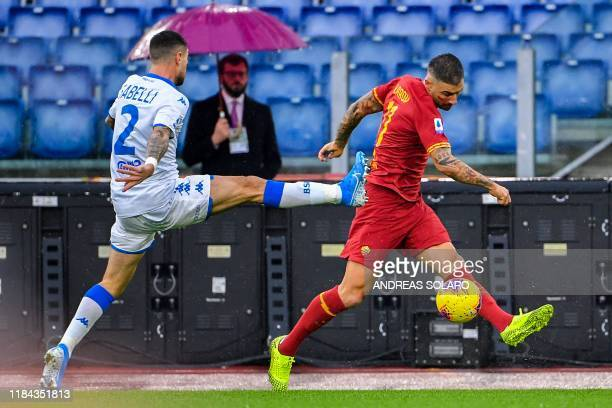 Brescia's Italian midfielder Stefano Sabelli attempts to tackle AS Roma's Serbian defender Aleksandar Kolarov during the Italian Serie A football...