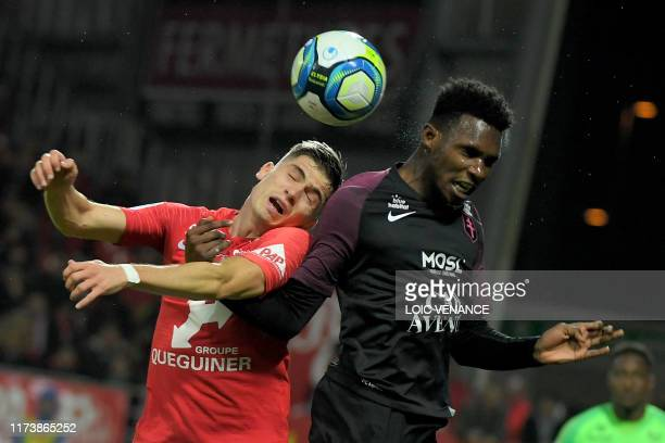 Brest' French defender Romain Perraud heads the ball with Metz' French-Senegalese midfielder Opa Nguette during the French L1 football match between...