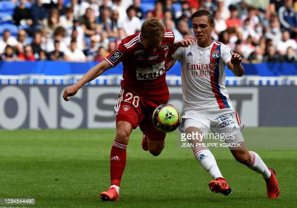 Brest's Finnish defender Jere Uronen fights for the ball with Lyon's French midfielder Maxence Caqueret during the French L1 football match between...