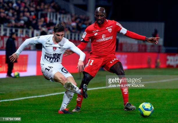 Brest's French defender Romain Perraud kicks the ball past Dijon's Cap Verdean forward Julio Tavares during the French L1 football match between...