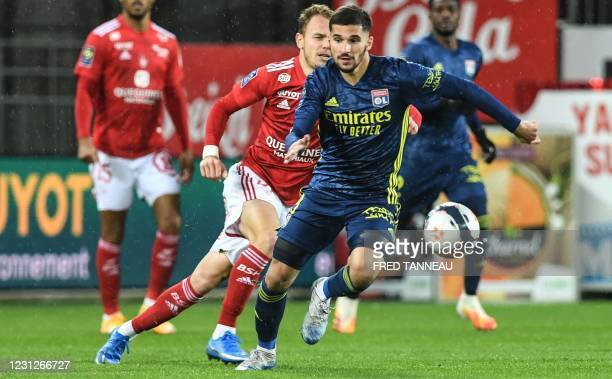 Brest's French forward Irvin Cardona fights for the ball with Lyon's French midfielder Houssem Aouar during the French L1 football match between...