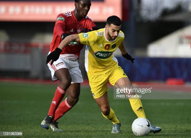 Brest's French midfielder Hiang'a Mbock challenges Rodez's French forward Ayoub Ouhafsa during the French Cup round-of-64 football match between...