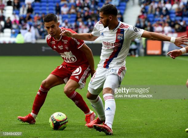 Brest's French midfielder Romain Faivre fights for the ball with Lyon's French midfielder Houssem Aouar during the French L1 football match between...