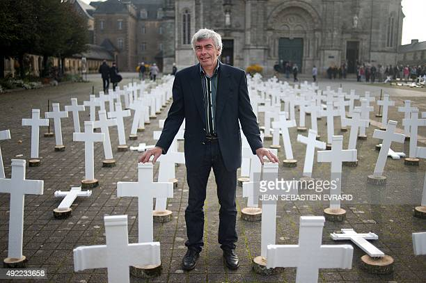 Breton farmer Jacques Jeffredo poses next to 600 white crosses in memory of all farmers who commit suicide every year on October 11 2015 in...