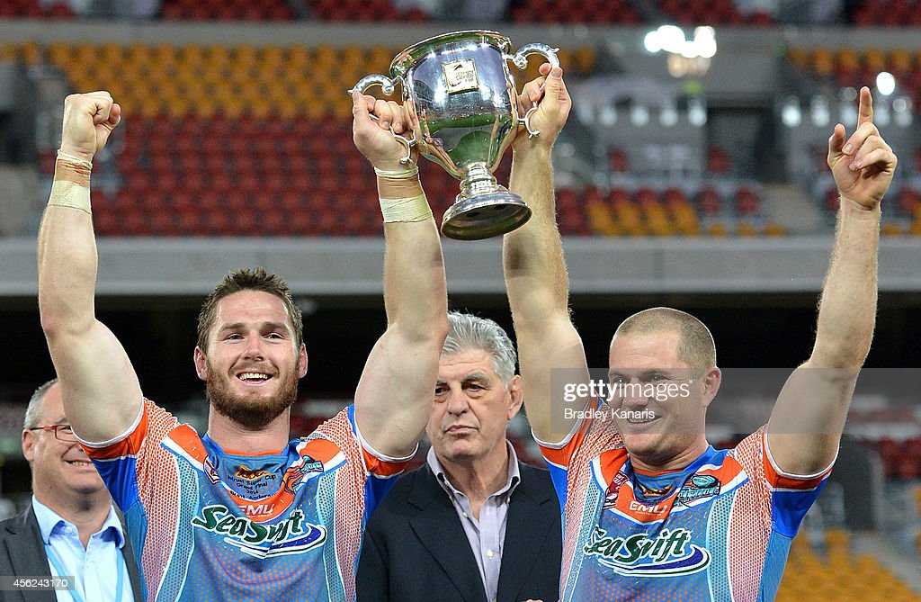 Brett Anderson and Jason Roos hold up the winners trophy after the Intrust Super Cup Grand Final match between Northern Pride and Easts Tigers at Suncorp Stadium on September 28, 2014 in Brisbane, Australia.