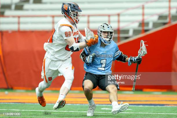 Brett Baskin of the Johns Hopkins Blue Jays dodges to the goal while being checked by Andrew Helmer of the Syracuse Orange during the first half at...