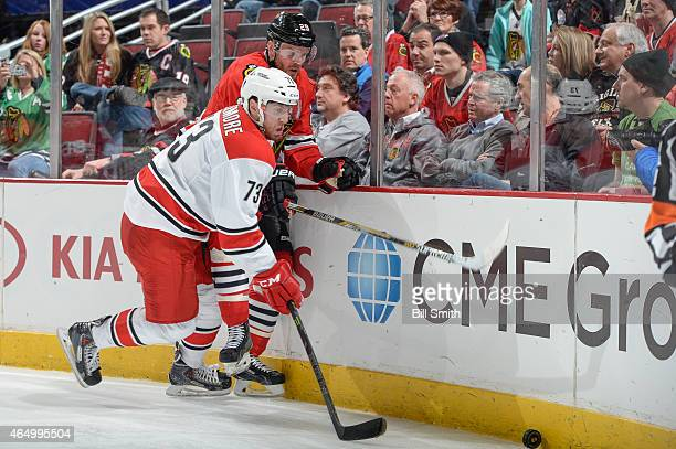 Brett Bellemore of the Carolina Hurricanes and Bryan Bickell of the Chicago Blackhawks chase the puck during the NHL game on March 02 2015 at the...