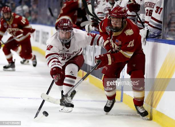 Brett Boeing of the Massachusetts Minutemen and Tyler Ward of the Denver Pioneers fight for the puck during the semifinals of the NCAA Men's Frozen...