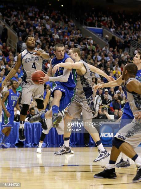 Brett Comer of the Florida Gulf Coast Eagles looks to pass the ball in the second half as he drives against Nate Lubick and D'Vauntes Smith-Rivera of...