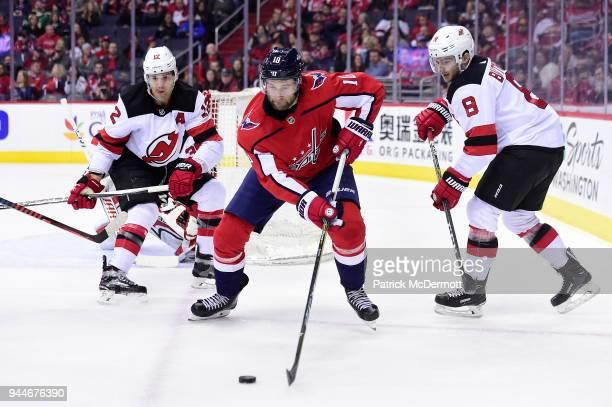 Brett Connolly of the Washington Capitals controls the puck against Will Butcher and Ben Lovejoy of the New Jersey Devils in the first period at...