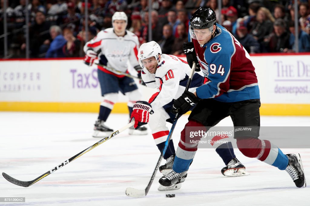 Brett Connolly #10 of the Washington Capitals fights for the puck against Andrei Mironov #94 of the Colorado Avalanche at Pepsi Center on November 16, 2017 in Denver, Colorado.