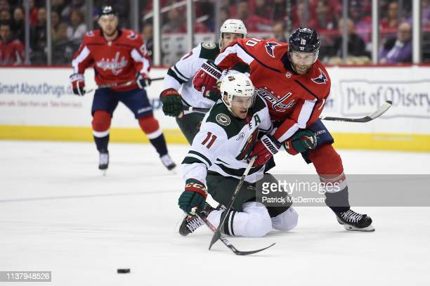 Brett Connolly of the Washington Capitals skates with the puck against Zach Parise of the Minnesota Wild in the first period at Capital One Arena on...