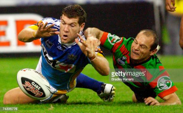 Brett Delaney of the Titans beats Reece Simmonds of the Rabbitohs to the ball to score a try during the round 11 NRL match between the Gold Coast...