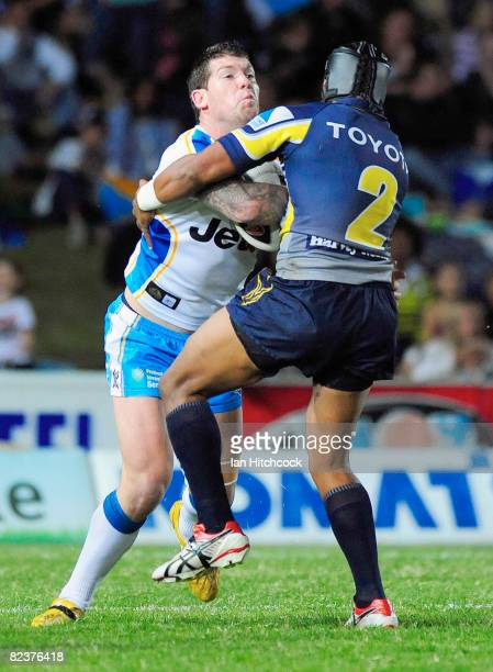 Brett Delaney of the Titans is tackled by Ty Williams of the Cowboys during the round 23 NRL match between the North Queensland Cowboys and the Gold...