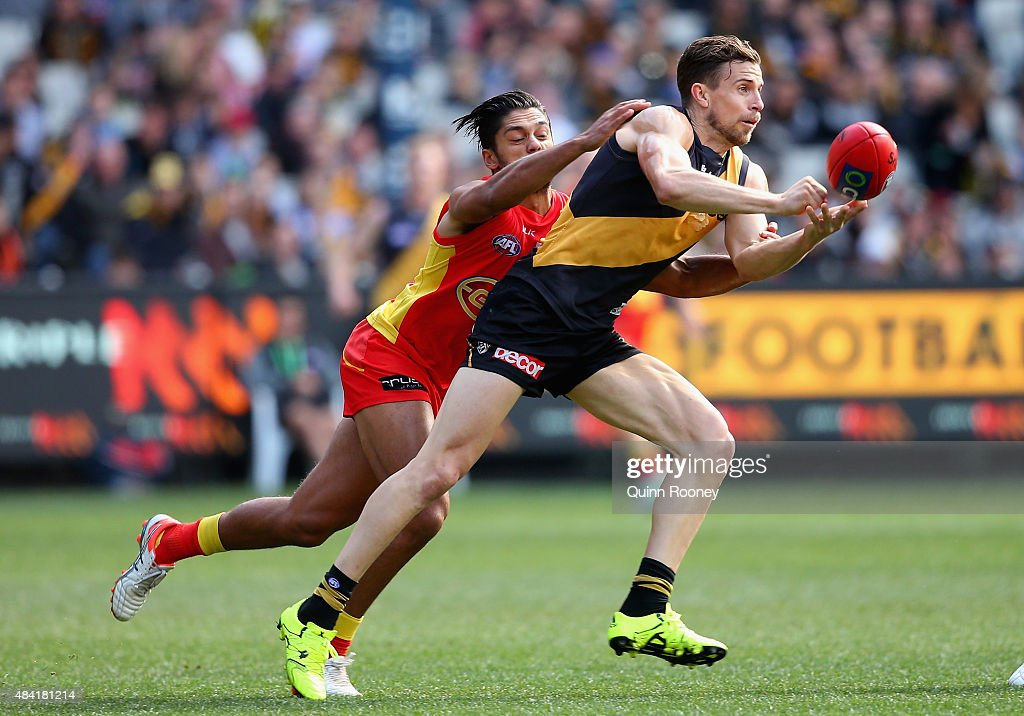 Brett Deledio of the Tigers handballs whilst being tackled by Aaron Hall of the Suns during the round 20 AFL match between the Richmond Tigers and the Gold Coast Suns at Melbourne Cricket Ground on August 16, 2015 in Melbourne, Australia.