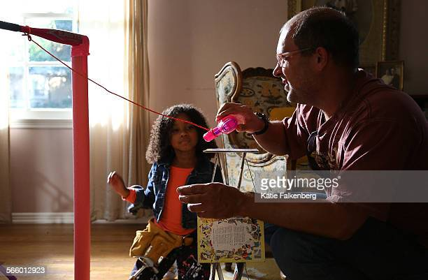 Brett Doar resets a part of a Rube Goldberg machine he designed and he and his team built in a home in Pasadena for a video for GoldieBlox a toy...