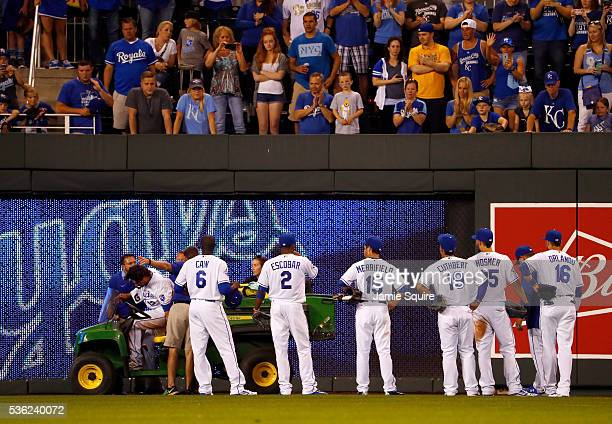 Brett Eibner of the Kansas City Royals is attended to by medical staff as players look on after going down with an injury during the 5th inning of...