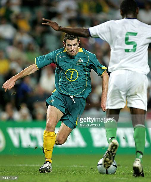 Brett Emerton of Australia attacks the ball as George Suri of the Solomon Islands prepares to defend during the second leg of the Oceania Nations Cup...