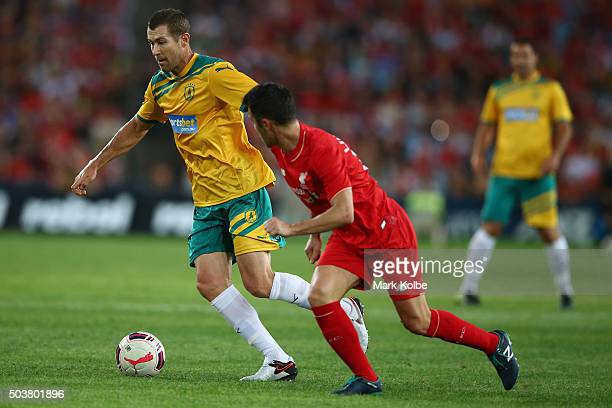 Brett Emerton of the Australian Legends takes the ball past Luis Garcia of the Liverpool FC Legends during the match between Liverpool FC Legends and...