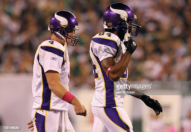 Brett Favre and Randy Moss of the Minnesota Vikings walk on the field in the second quarter against the New York Jets at New Meadowlands Stadium on...