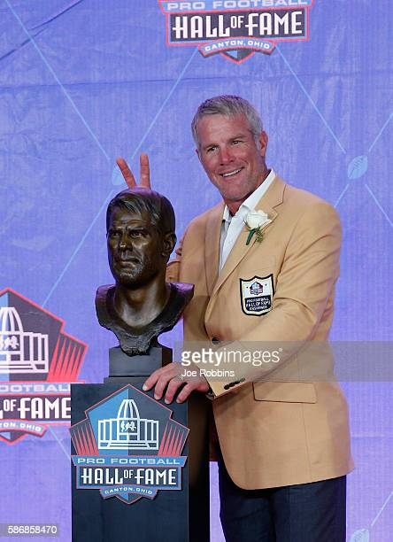 Brett Favre former NFL quarterback poses with his bronze bust during the NFL Hall of Fame Enshrinement Ceremony at the Tom Benson Hall of Fame...