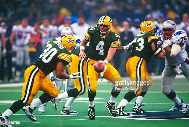 Brett Favre of the Green Bay Packers turns to hand the ball off to running back William Henderson against the New England Patriots during Super Bowl...