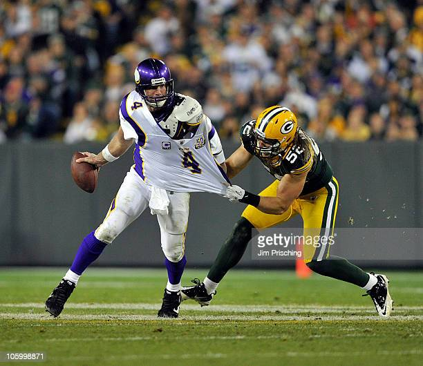 Brett Favre of the Minnesota Vikings has his jersey grabbed by Clay Matthews of the Green Bay Packers at Lambeau Field on October 24 2010 in Green...