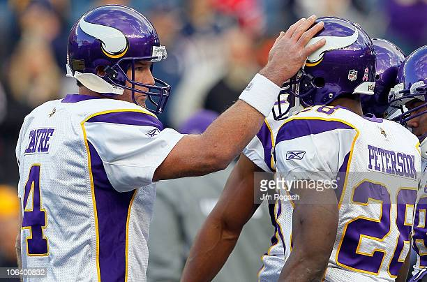 Brett Favre of the Minnesota Vikings interacts with teammate Adrian Peterson before a game against the New England Patriots at Gillette Stadium on...