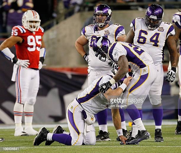 Brett Favre of the Minnesota Vikings is aided by teammate Adrian Peterson after Favre was hit by Myron Pryor of the New England Patriots in the...